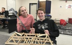 Seniors Sara Hoskins and Peyton Weisbeck pose for a photo with their submission for the Bridge Building Contest in the high school engineering room. The contest was held in March 2019.