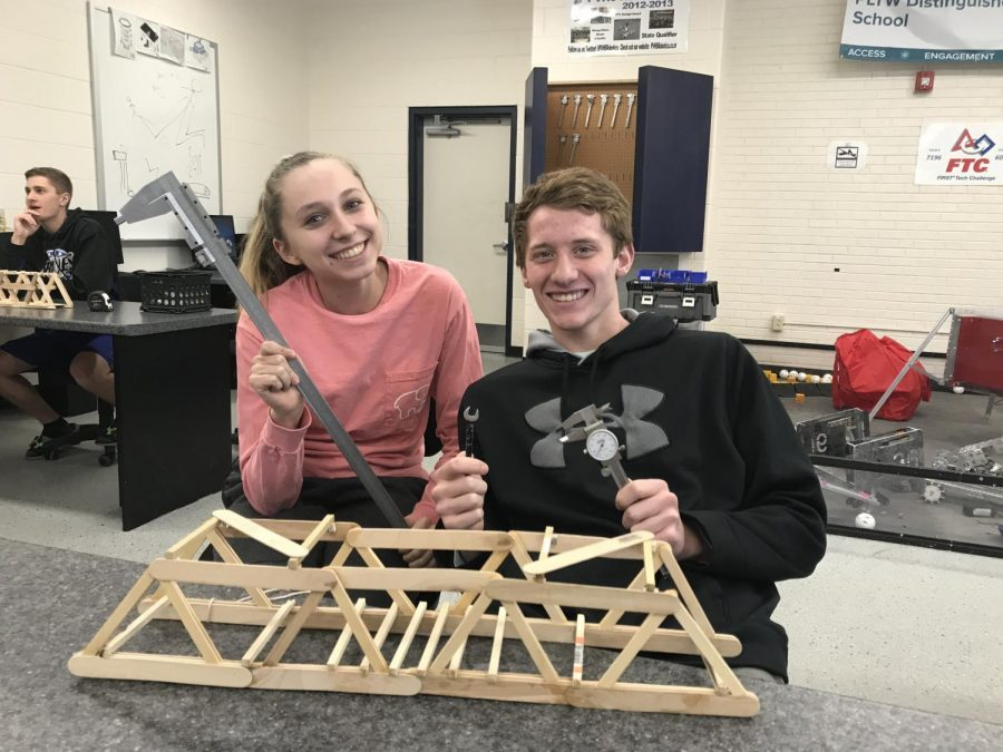 Seniors+Sara+Hoskins+and+Peyton+Weisbeck+pose+for+a+photo+with+their+submission+for+the+Bridge+Building+Contest+in+the+high+school+engineering+room.+The+contest+was+held+in+March+2019.