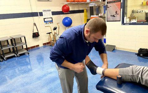 Jason Viel tapes up freshman Rusty VanWetzinga's ankle before his wrestling practice.