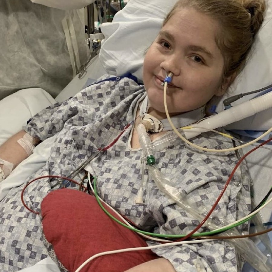 Analiese Chapman smiling in her hospital bed after getting a breathing tube put in.