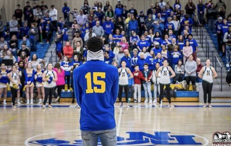 Jamal Litt, Davenport North varsity basketball player, attends basketball game against Pleasant Valley, where both student sections dressed in his favorite color in support of him and his accident.