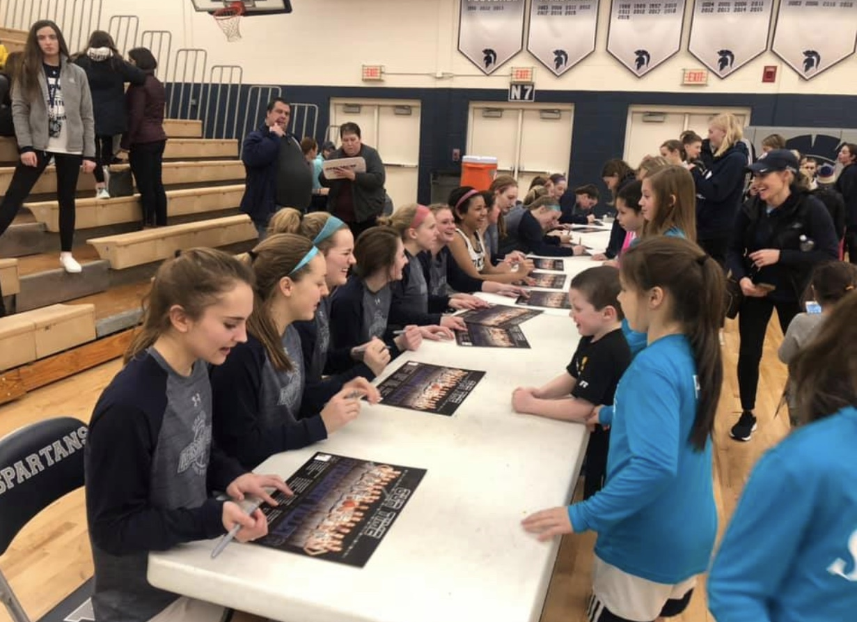 Pleasant Valley Girl's Basketball team signing posters for future Spartans at youth night.