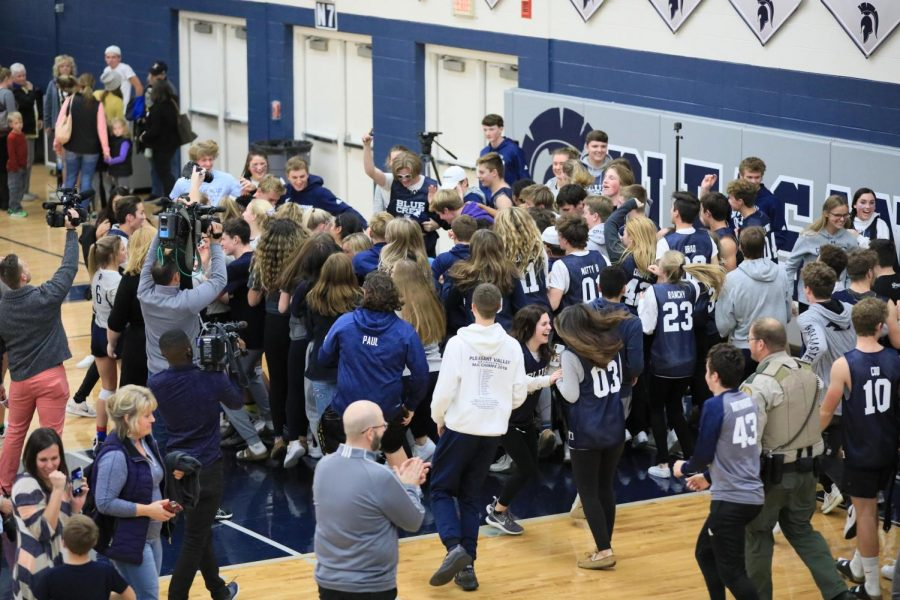 Spartan student section runs onto the court to celebrate with the 2019 Volleyball team after their regional final win against Bettendorf.