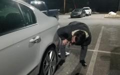Senior Bradley Hamilton inspects one of his car's wheels well for accumulated salt.