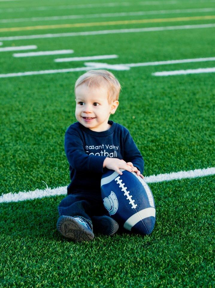 Will Kohn, smiling bright while sitting on Pleasant Valley's football field.