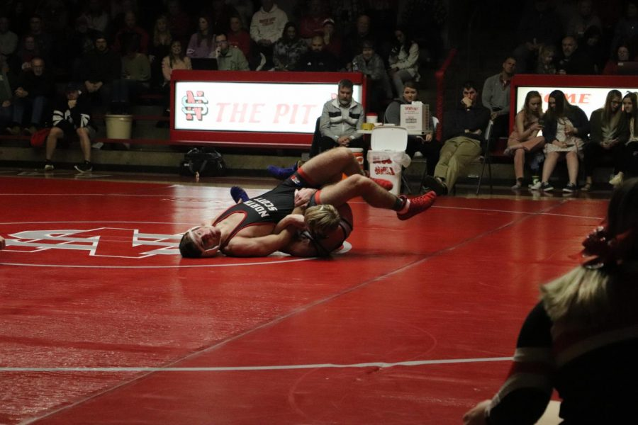 Senior Eli Lloyd attempts to pin opponent at North Scott wrestling meet.