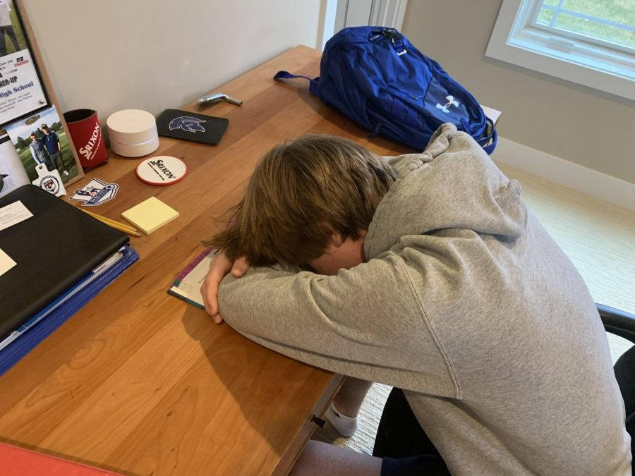 Senior Lucas Wood falls asleep in a textbook while trying to do school work.