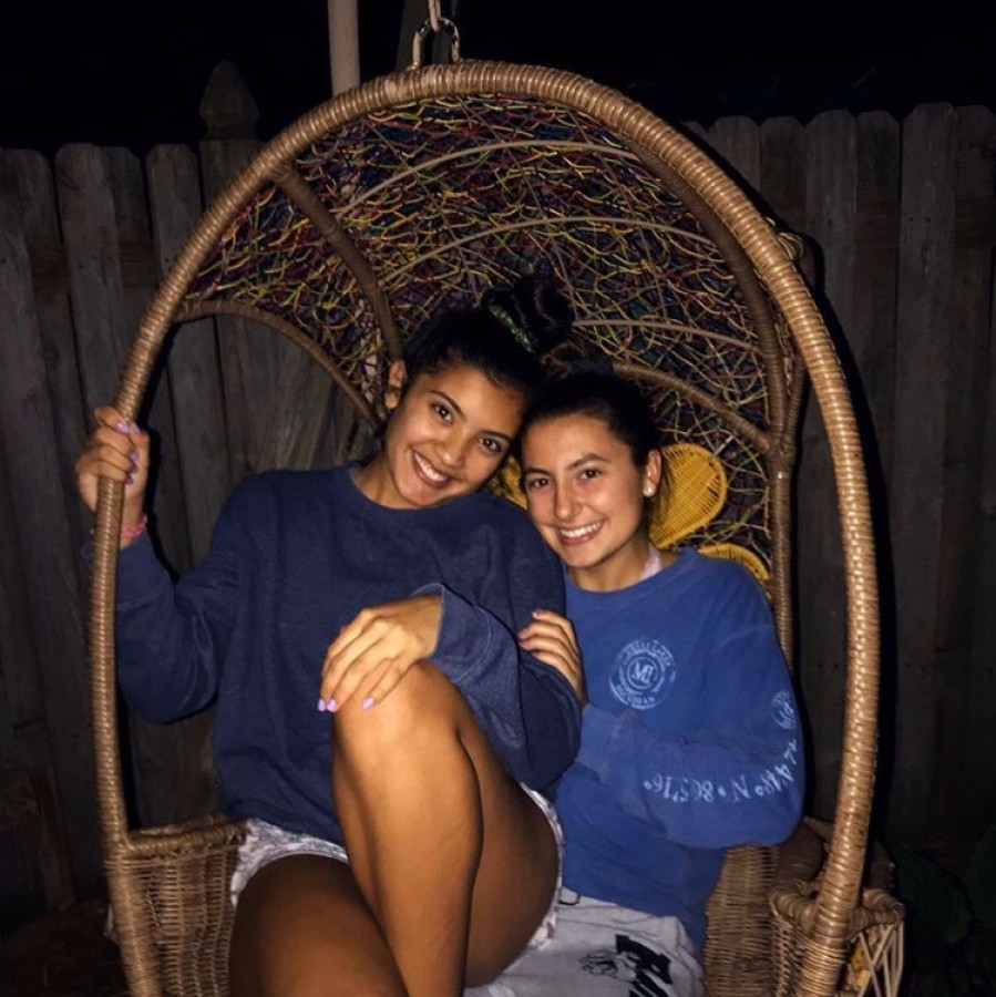 Lifetime lovers and seniors Cienna Pangan and Kate Stewart sit in a hanging chair together.