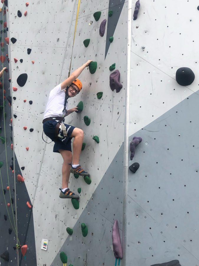 Seventh grader Avyn Nelson smiling while climbing a rock wall in Chicago, Illinois