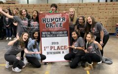 Members of Spartan Assembly hold the banner stating that Pleasant Valley won first place for the student hunger drive while at the Riverbend Food Bank.