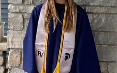 Senior Maya Johnson poses for a picture wearing her cap and gown.