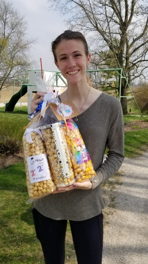 "Senior Katie Garner holds a basket of popcorn that she received from a parent through the ""Adopt a Senior"" Facebook page."