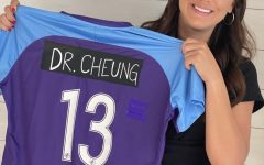 Professional soccer player, Alex Morgan, holds up one of her jerseys with Dr. Cheung's name taped over hers.