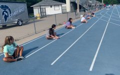 A group of cheerleaders stretch socially distanced at their outdoor practice.