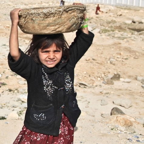 An impoverished, school-age female of a developing country does arduous labor in the fields to support her family while schools remain closed.