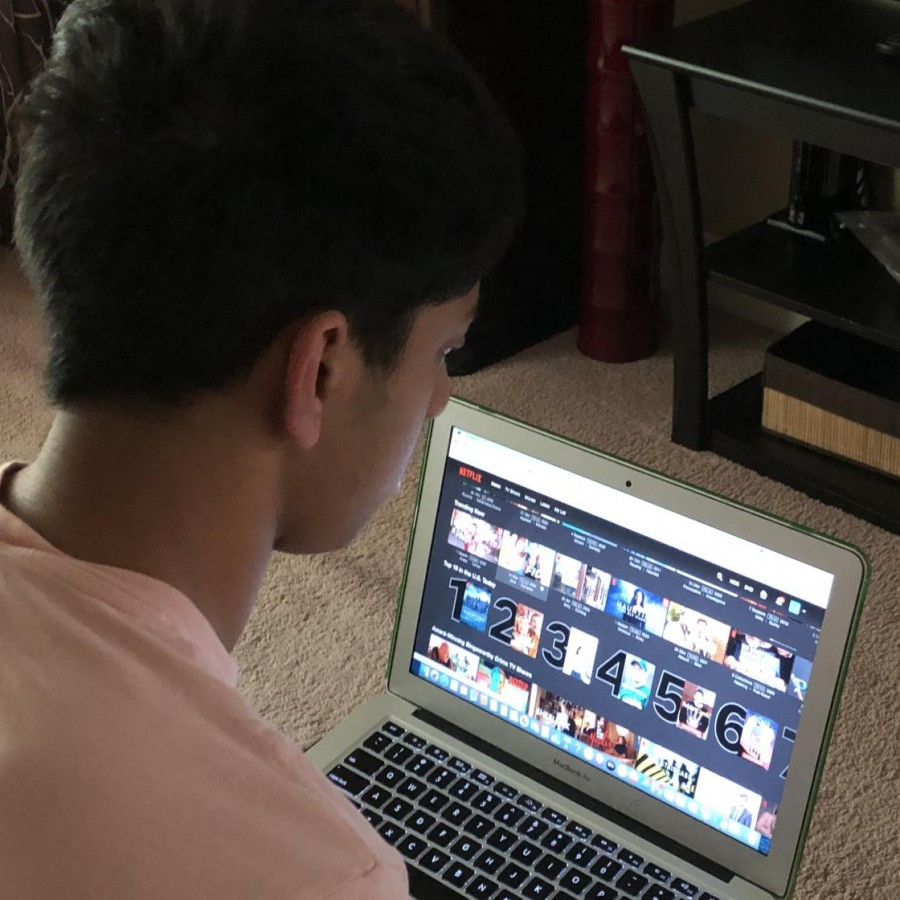 "Senior Akash Pradeep scrolls through the Netflix home screen in search of his favorite show, ""The Office."" This is one of the reasons that many viewers, like Pradeep, remain loyal to the monopolizing streaming service."
