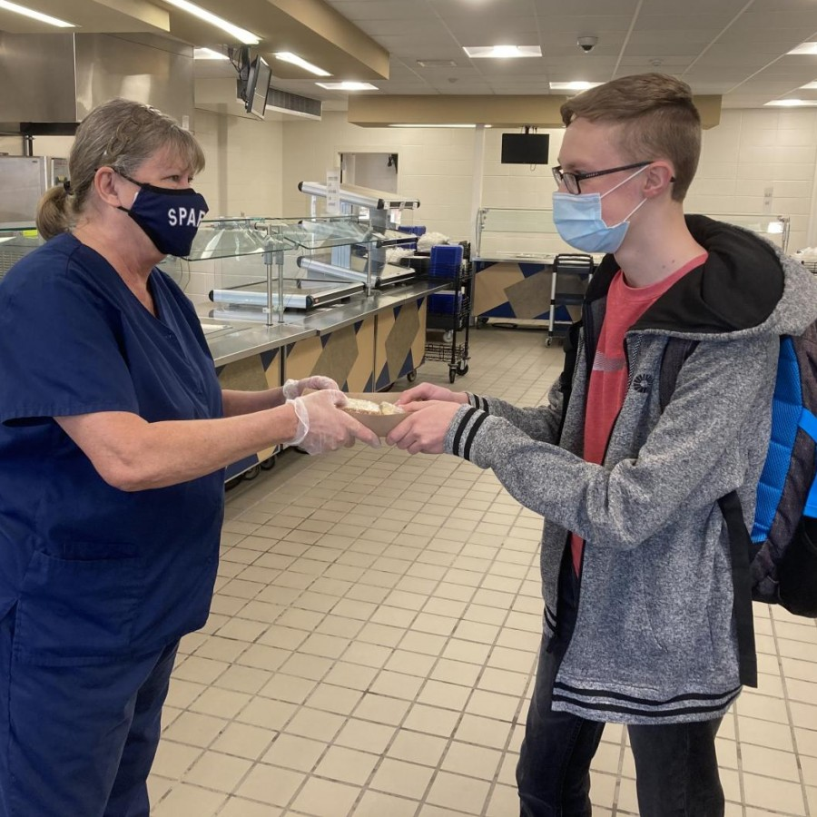 Food service worker Robin Funk hands gluten-free and dairy-free food to senior Jonathan Sulgrove.