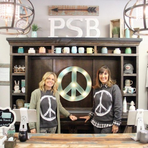Local small business owners Linda Mowbray and Chris Slavens posing in their boutique, Peaceful Style.