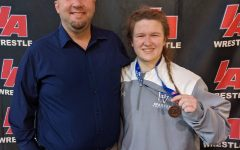Junior Aine Moffitt and her coach, Tom Isaacson, after she placed 4th at the girls wrestling state championship tournament on Jan. 23 and 24.
