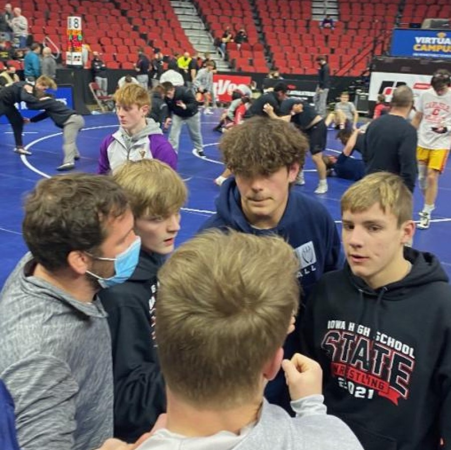 The PV state qualified wrestlers in huddles before the first day of wrestling at the state tournament.