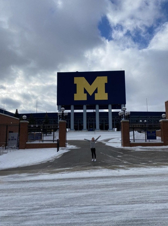 Sarah Babka stands in front of the University of Michigan, beaming with excitement, during her college visit.