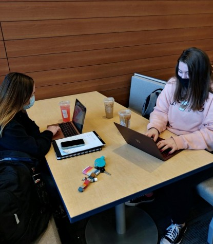 Seniors Reese Wendall and Anali Anderson drinking Starbucks and completing homework before class.