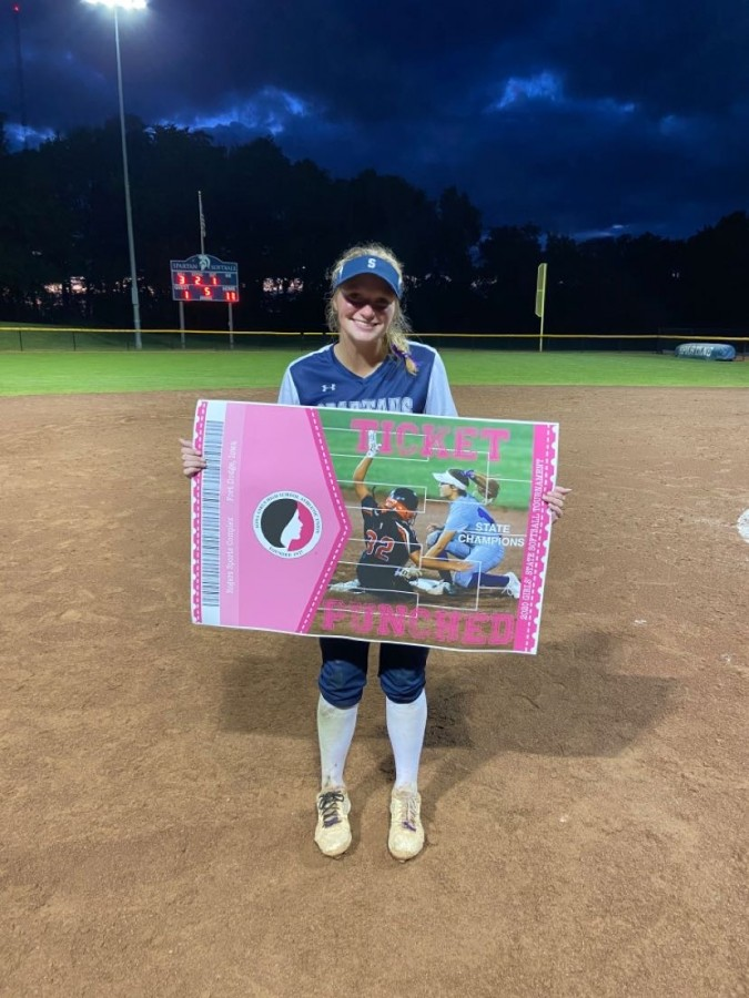 Jessi Meyer posing with the state participant banner after winning the substate final game during her junior season
