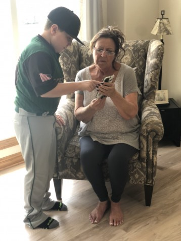Lane Roberts taking the time to help his grandmother, Polly Cotton, figure out her phone.