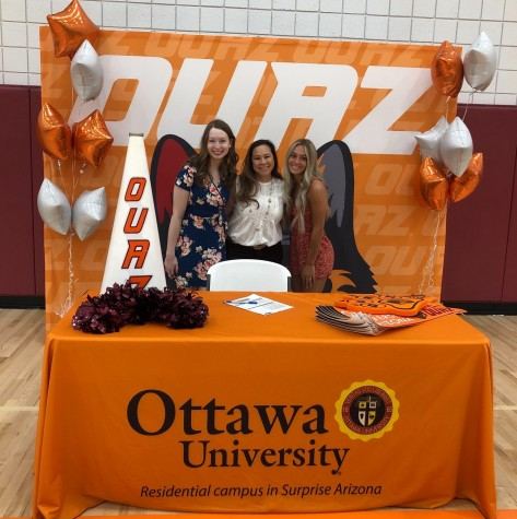 Seniors Addi Steele and Macie Skahill sign on to their cheer team in Arizona with their new coach, Kari Kratchman.