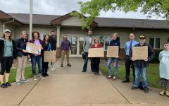Community members gather outside the Belmont administrative building with signs urging the board to repeal its mask mandate before the May 18 board meeting.