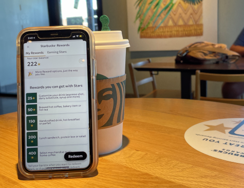 A student earns stars towards free coffee on their Starbucks rewards app after buying a new fall drink.