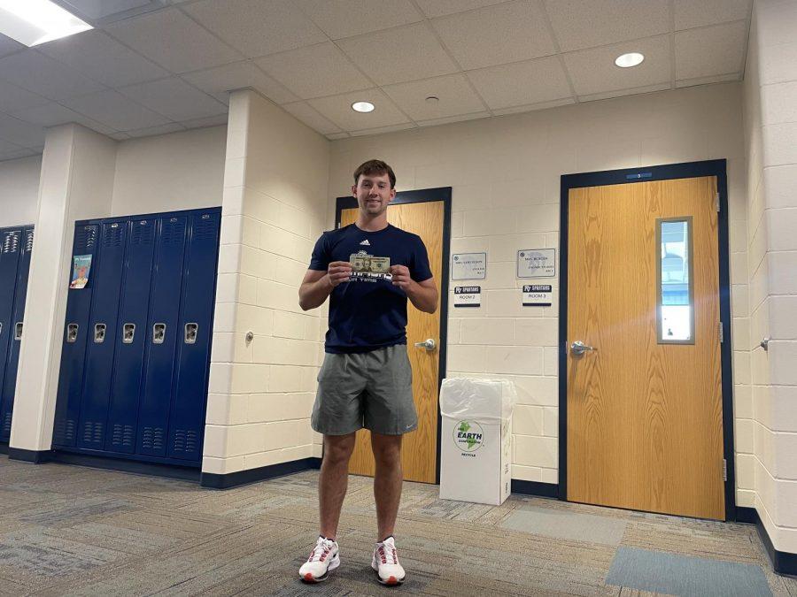 Senior Brady Hunter holds up a 20 dollar bill on Thursday morning exemplifying his commitment to saving money.