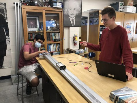 Seniors Vishnu Challa (left) and Nathan Romans (right) doing the Cart on a Ramp lab in AP Physics.