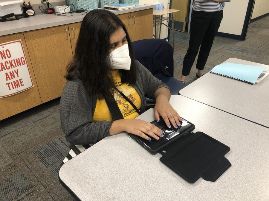 Sophomore Niyati Patel using her BraileSense educational tool to complete her homework for the day.