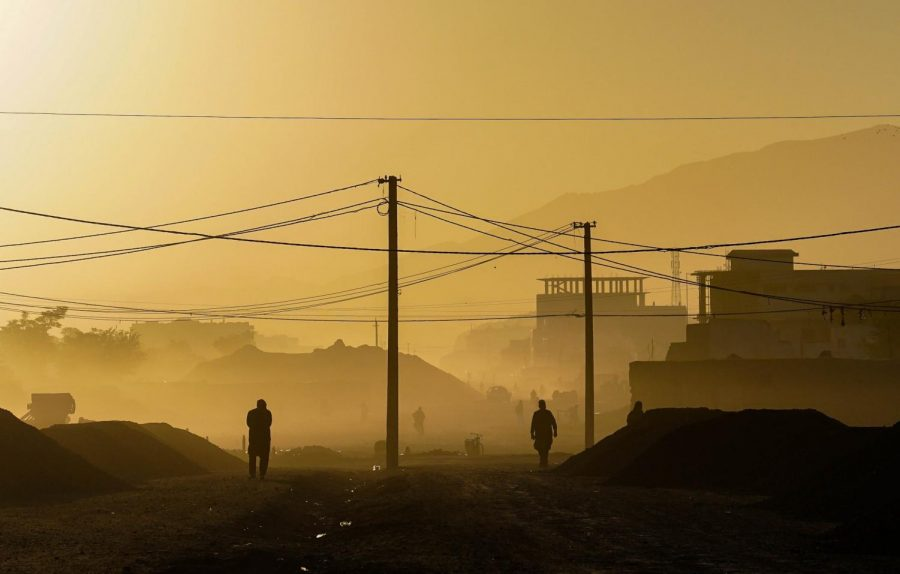 Citizens walk through Kabul at sunrise as the takeover and Taliban invasion plagues Afghanistan.