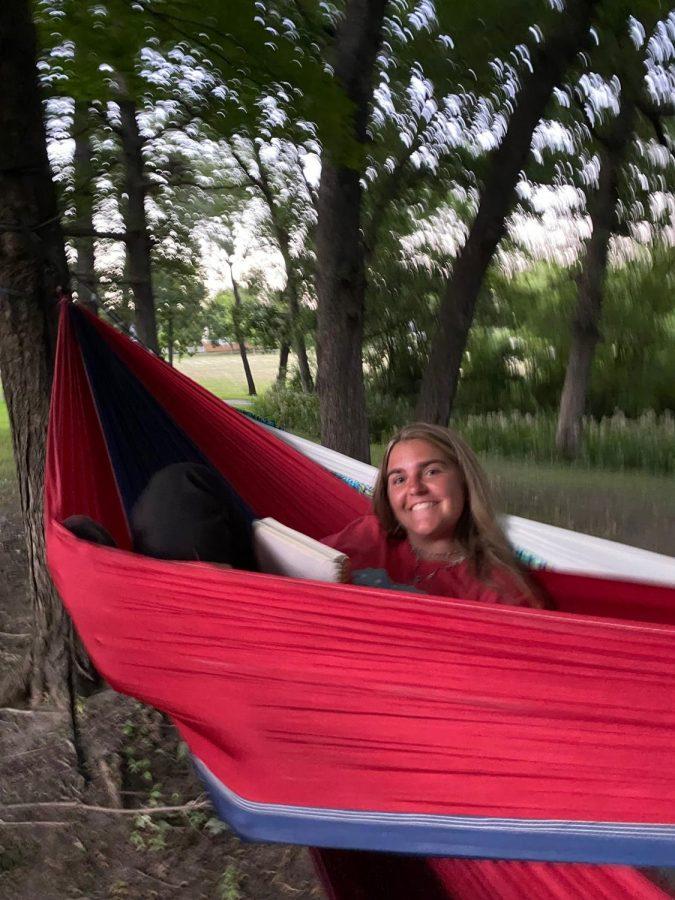 Senior Lily Dumas hammocks and journals in Devils Glen park.