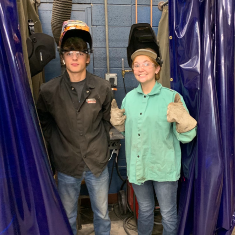 Seniors Brady Meyrer and Lauren Puthoff lift their masks for a photo in their welding class.