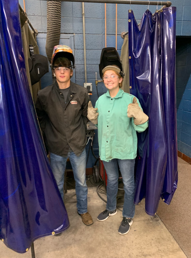 Seniors+Brady+Meyrer+and+Lauren+Puthoff+lift+their+masks+for+a+photo+in+their+welding+class.